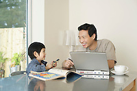 Father and son sitting at kitchen table together; laptop and coloring book on table
