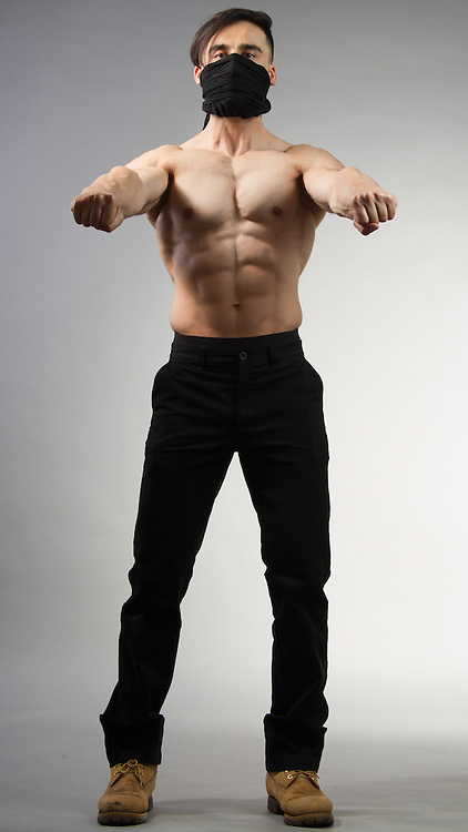 Male model posiing shirtless with a scarf wrapped around his face.