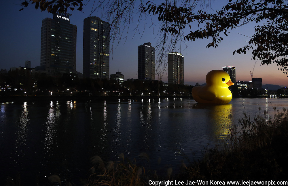 "A gigantic rubber duck designed by Dutch artist Florentijn Hofman is seen floating in Seokchon Lake in Seoul November 14, 2014. The 300 kg, 54-foot tall rubber duck has been displayed in Seoul from October 14, 2014 until November 14, 2014 as part of a promotion for Lotte World Tower. The ""Rubber Duck Project"" has traveled to various cities since 2007 to ""heal wounds"" and ""relive tension"". / Lee Jae-Won"