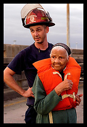 29th August, 2005. Hurricane Katrina hits New Orleans, Louisiana. Fireman Neil Dugas helps 92yr old Irma Simmons evacuate the lower 9th ward after it suffered catastrophic flooding.