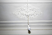 old classic ornamental ceiling with bare single light bulb