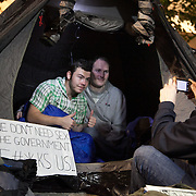 A couple of protestors in their tent. The London Stock Exchange was attempted occypied in solidarity with Occupy Wall in Street in New York and in protest againts the economic climate, blamed by many on the banks. Police managed to keep people away fro the Patornoster Sqaure and the Stcok Exchange and thousands of protestors stayid in St. Paul's Square, outside St Paul's Cathedral. Many camped getting ready to spend the night in the square.
