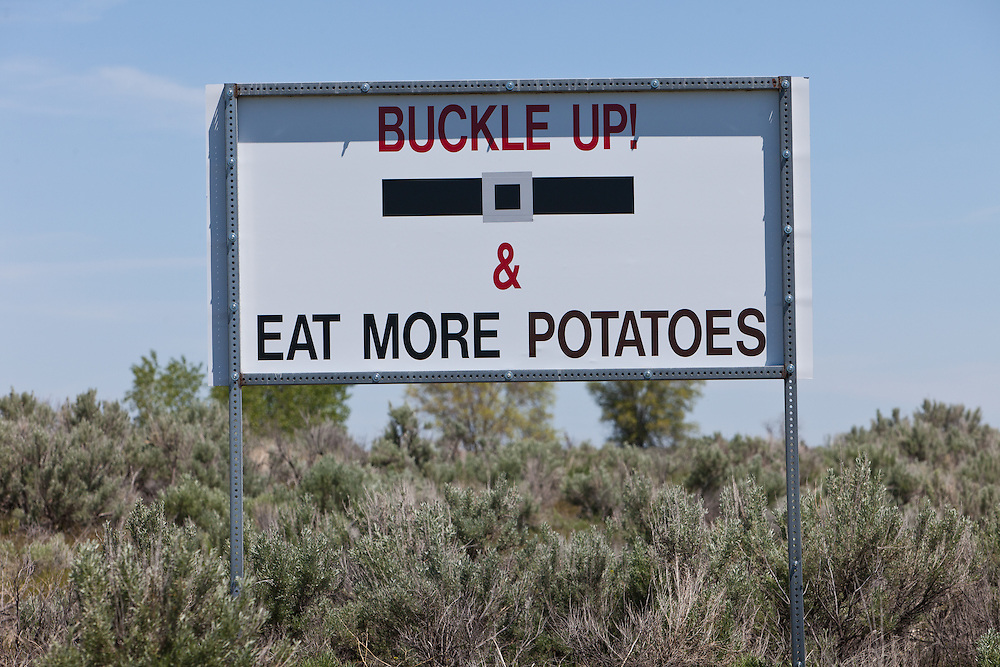 Flip side of welcome sign to the Historical town of Pingree along the Snake River near American Falls Reservoir in Southeastern Idaho would like you to buckle up and eat more potatoes