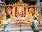 07 OCTOBER 2012 - BANGKOK, THAILAND:  People walk past a portrait of Bhumibol Adulyadej, the King of Thailand, in front of the C.P. Tower in Bangkok. Bhumibol Adulyadej is the reigning King of Thailand. He is known as Rama IX. Having reigned since 9 June 1946, he is the world's longest-serving current head of state and the longest-reigning monarch in Thai history. He is revered by the Thai people, his birthday, Dec. 5, is a national holiday and is also celebrated as Father's Day in Thailand. As the King's Birthday approaches, businesses put up giant portraits of the King in front of their buildings.    PHOTO BY JACK KURTZ