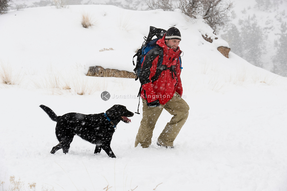 Side view of a mid adult man wearing a red jacket and backpack walking in the snow with a black dog in Bend, Oregon. (releasecode: jk_mr1036) (Model Released)