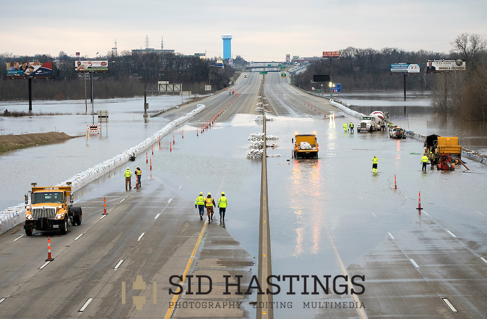 31 DEC. 2015 -- ARNOLD, Mo. -- Workers from the Missouri Department of Transportation attempt to pump water off I-55 near Arnold, Missouri USA Thursday, December 31, 2015. Flooding from the nearby Meramec River, a tributary of the Mississippi River, flooded the highway, closing the main artery between St. Louis and Memphis. MoDOT crews installed a sandbag wall to protect the highway and were attempting to pump out water trapped behind the temporary flood wall. Historic rainfall across the American Midwest has pushed the Meramec and other rivers in Missouri to record levels. Photo © copyright 2015 Sid Hastings.