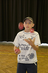 Young boy juggling in school sports hall,