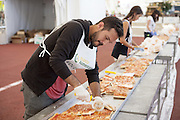 Food Bank volunteers cut and package 300 meters of pizza for six reception centers in Milan managed by associations that deal with social difficulties, Expo 2015, Rho-Pero, Milan, 20 June 2015. The pizza is part of a &quot;pizza margherita&quot; 1,595.45 meters long and weighing five tons which entered into the Guinness Book of Records as the world's longest pizza. &copy; Carlo Cerchioli <br /> <br /> Volontari del Banco alimentare tagliano e confezionano 300 metri di pizza destinati a sei centri di accoglienza di Milano gestiti dalle associazioni che si occupano di disagio sociale, Expo 2015, Rho-Pero, Milano, 20 giugno 2015. La pizza fa parte di un &quot;margherita&quot; lunga 1595,45 metri pesante cinque tonnellate e che &egrave; entrata nel Guinnes dei primati come la pizza pi&ugrave; lunga del mondo.