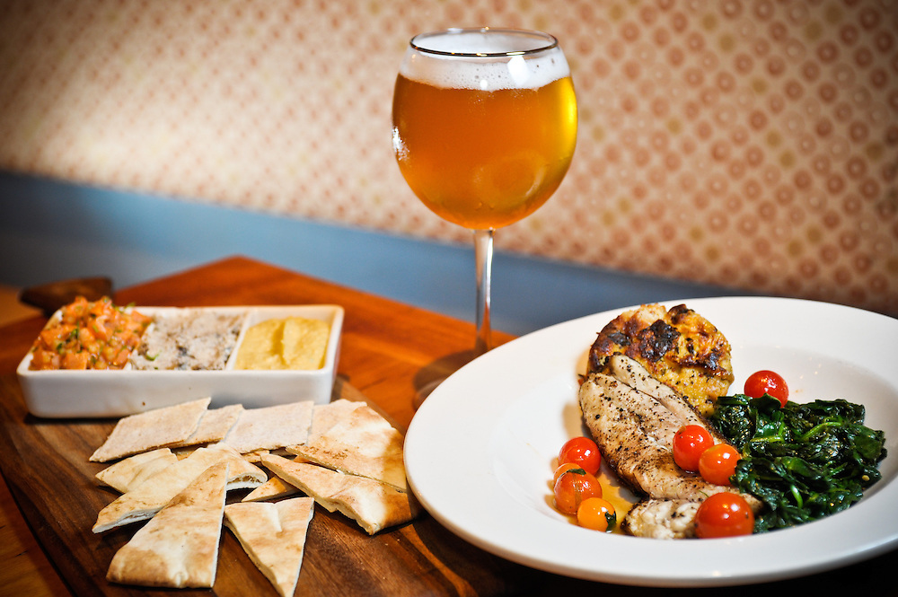 Hummus and fish dishes with beer at a booth in the Ashmont Grill in Dorchester, MA.