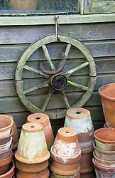 Terracotta pots, cartwheel and horseshoe decorating outside of greenhouse