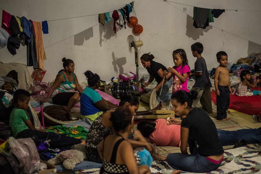 TENOSIQUE, MEXICO - MAY 29, 2014:  Women and children prepare to go to sleep at the 72 migrant shelter in Tenosique, where  Catholic priests and other volunteers provide mats for migrants to sleep on, second-hand clothes, meals, basic medical treatment, and help applying for immigration visas and refugee status to people traveling north. The shelter, which traditionally has been visited by men between the ages of 15-35, has been overrun by women and children in recent months, more than double the amount -- consequential of a recent boom of minors headed to the United States from Central America. PHOTO: Meridith Kohut for The New York Times