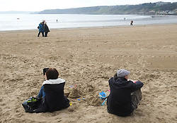 © Licensed to London News Pictures. <br /> 05/04/2015. <br /> <br /> Scarborough, United Kingdom<br /> <br /> A couple sit on the sand on the beach at Scarborough on Easter Sunday.<br /> <br /> Photo credit : Ian Forsyth/LNP