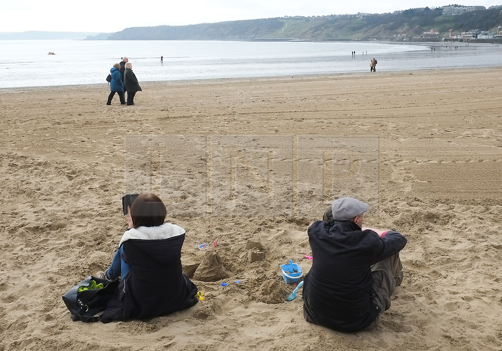 &copy; Licensed to London News Pictures. <br /> 05/04/2015. <br /> <br /> Scarborough, United Kingdom<br /> <br /> A couple sit on the sand on the beach at Scarborough on Easter Sunday.<br /> <br /> Photo credit : Ian Forsyth/LNP
