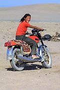 GOBI DESERT, MONGOLIA..08/29/2001.Tzochorinam, gers belonging to the family of wealthy camel herder and local hero Chimiddorj. Girl on motorbike..(Photo by Heimo Aga).