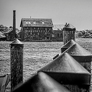 This is an old manufacturing building in Gloucester, MA.  I was looking out across the water and took quite some time to get the building framed in the dock pilings.