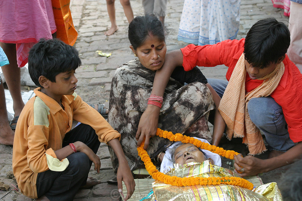 Durga Tiwari, 35, attends to her dead mother, Savitridevi Mishra, just before she is taken to the cremation grounds of Jalasi Ghat.