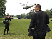 (left) White House Staff Photographer David Bohrer photographs crowd reaction as Marine One flys to Andrews Airforce Base from the South Lawn of The White House with President Bush on board.  (right) Eric Draper, the official photographer to the President, stands by looking for other photographic opprotunities. Bush was on his way to Andrews where he boarded Air Force One for a trip to Kansas City Mo.  Bohrer is the personal photographer for Vice President Dick Cheney, however he fills in on many events at the White House. Bohrer is a San Fernando Valley resident, who along with Morse and Draper, graduated from U.C. Long Beach.