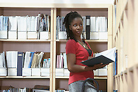 Office worker holding book standing on ladder in file storage room