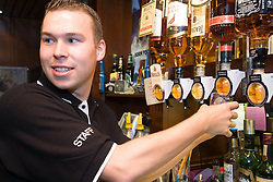 Young Polish barman using optic to measure drink at Polish Social Club,