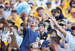 Sep 16, 2017; Morgantown, WV, USA; A West Virginia Mountaineers fan hits a ball in the stands during the first quarter against the Delaware State Hornets at Milan Puskar Stadium. Mandatory Credit: Ben Queen-USA TODAY Sports