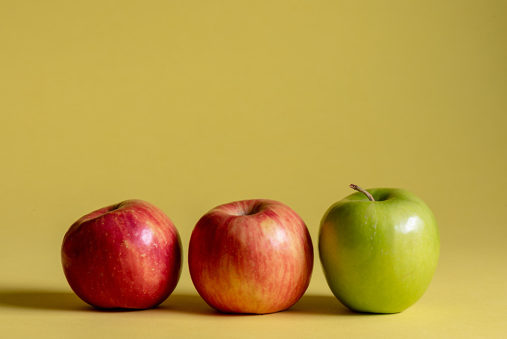 Two red and one green apple on a yellow background.