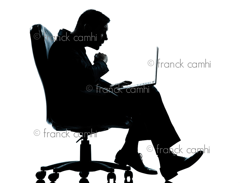 one caucasian business man computer computing surprised sitting in armchair silhouette Full length in studio isolated on white background