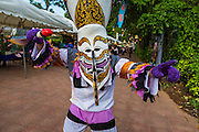 """27 JUNE 2014 - DAN SAI, LOEI, THAILAND: A """"ghost"""" in downtown Dan Sai during the Phi Ta Khon. Phi Ta Khon (also spelled Pee Ta Khon) is the Ghost Festival. Over three days, the town's residents invite protection from Phra U-pakut, the spirit that lives in the Mun River, which runs through Dan Sai. People in the town and surrounding villages wear costumes made of patchwork and ornate masks and are thought be ghosts who were awoken from the dead when Vessantra Jataka (one of the Buddhas) came out of the forest.    PHOTO BY JACK KURTZ"""