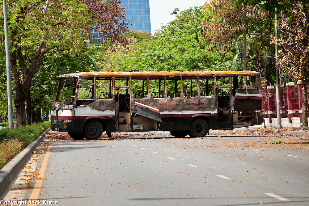 20 MAY 2010 - BANGKOK, THAILAND: A burnt out bus blocks Witthayu Road near the US Embassy in Bangkok Thursday. The bus was destroyed during street fighting the day before. The day after a military crackdown killed at least six people, Thai authorities continued mopping up operations around the site of the Red Shirt rally stage and battle fires set by Red Shirt supporters in the luxury malls around the intersection. PHOTO BY JACK KURTZ