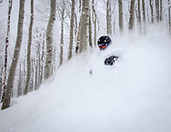 An alpine skier descends through deep powder snow as the light, fluffy snow blows up in his face,  nearly covering the skier. http://www.gettyimages.com/detail/photo/alpine-skier-descending-in-a-cloud-of-powder-snow-royalty-free-image/150652730