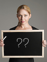 Portrait of young businesswoman holding blackboard with question marks