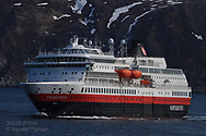 Hurtigruten cruise ship, Finnmarken, sails along coastal cliffs  in early May near Havoysund, Norway.