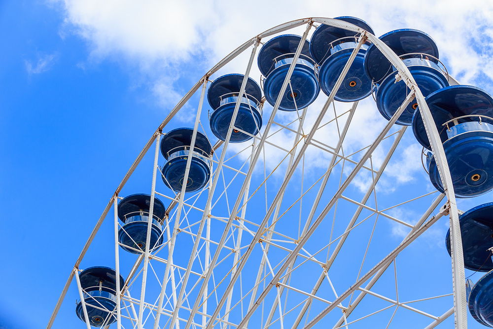 A Ferris wheel at the ocean at an amusement rides area on the boardwalk.