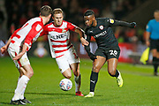 Herbie Kane of Doncaster Rovers  and Barnsley forward Mamadou Thiam (26) contest a loose ball  during the EFL Sky Bet League 1 match between Doncaster Rovers and Barnsley at the Keepmoat Stadium, Doncaster, England on 15 March 2019.