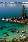 Secret Cove at Lake Tahoe with snow covered mountains in the background.