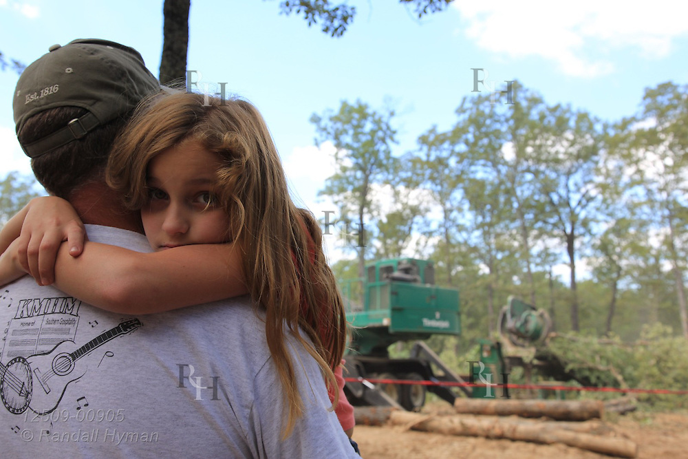 Girl rests in dad's arms during ultra-mechanized clearcutting of an Ozarks woodland at Missouri In Woods Logging Demo near Viburnum, Missouri.