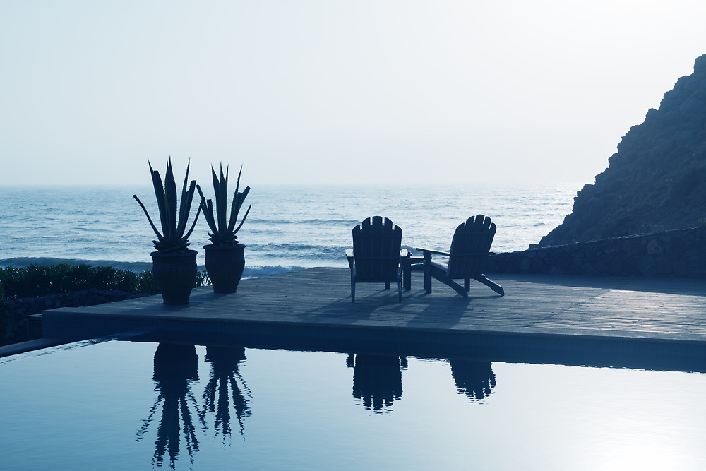 Two wooden relaxing chairs next to a swimming pool overlooking the sea.