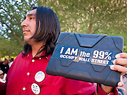 16 OCTOBER 2011 - PHOENIX, AZ: An Occupy Phoenix protester holds up a sign he put on the back of his iPad in downtown Phoenix Sunday evening. About 200 people continued the Occupy Phoenix protest in downtown Phoenix Sunday afternoon. The protest peaked Saturday afternoon at about 2,000 people. Nearly 50 people were arrested late Saturday night on misdemeanor trespassing charges when they tried to camp in a park near downtown and on Sunday the crowd dwindled to 200. Protesters hope to continue the protest through Monday by marching around downtown and picketing banks in the area.     PHOTO BY JACK KURTZ