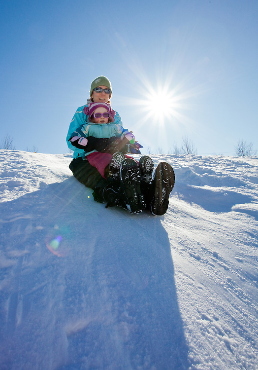 Mother and child (Katy Farber/Elly Budliger) slidding down a snowy hill in Vermont