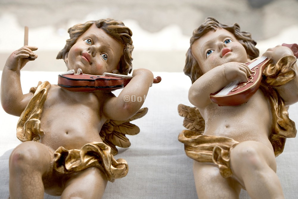 two music playing cherubs displayed at a flee market