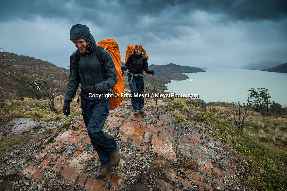 Patagonia, Chile, February 2016.  Hikers on the 'W' on their way to the Grey Glacier Lookout. The most highly trekked route in Torres del Paine National Park is called the 'W'. This trail system can be done in a variety of ways, from more rugged camping style treks, to full room and board in refugios. The W Circuit is named after its trail system that navigates up and down out of the mountain valleys. Torres del Paine is a UNESCO World Biosphere Reserve and encompasses mountains, glaciers, lakes, and rivers in southern Chilean Patagonia. The Cordillera del Paine is the centerpiece of the park. It lies in a transition area between the Magellanic subpolar forests and the Patagonian Steppes. A 4x4 camper is one of the best vehicles to explore the wild interior of Southern Patagonia. Photo by Frits Meyst / MeystPhoto.com