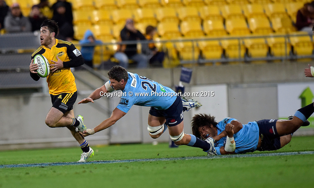 Hurricanes' fullback Nehe Milner-Skudder (L) runs out of a tackle by Waratahs' Tatafu Polota-Nau (Bottom) and Jacques Potgieter during the Super Rugby - Hurricanes v Waratahs rugby union match at the Westpac Stadium in Wellington on Saturday the 18th of April 2015. Photo by Marty Melville / www.Photosport.co.nz