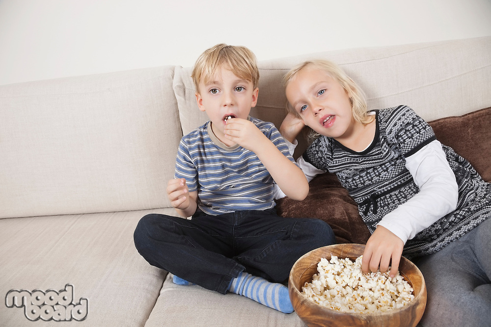 Brother and sister watching TV and eating popcorn