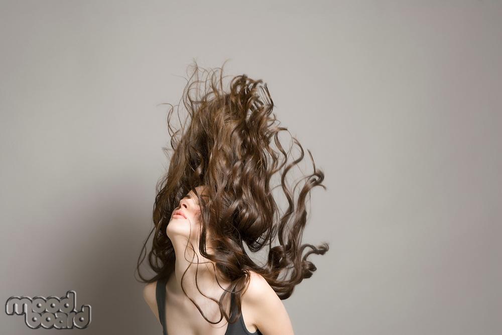 Woman tossing long brown wavy hair