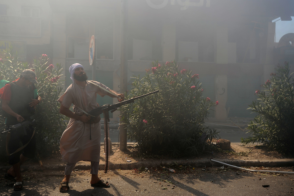 A rebel fighter prepares to shoot against enemy sniper positions in central Zawiyah.