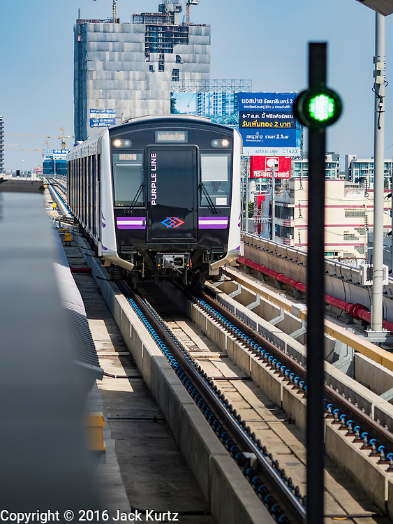 "23 AUGUST 2016 - NONTHABURI, NONTHABURI, THAILAND:  A Purple Line train pulls into a station on the ""Purple Line,"" the new Bangkok commuter rail line that runs from Bang Sue, in Bangkok, to Nonthaburi, a large Bangkok suburb. The Purple Line is run by the  Metropolitan Rapid Transit (MRT) which operates Bangkok's subway system. The Purple Line is the fifth light rail mass transit line in Bangkok and is 23 kilometers long. The Purple Line opened on August 6 and so far ridership is below expectations. Only about 20,000 people a day are using the line; officials had estimated as many 70,000 people per day would use the line. The Purple Line was supposed to connect to the MRT's Blue Line, which goes into central Bangkok, but the line was opened before the connection was completed so commuters have to take a shuttle bus or taxi to the Blue Line station. The Thai government has ordered transit officials to come up with plans to increase ridership. Officials are looking at lowering fares and / or improving the connections between the two light rail lines.    PHOTO BY JACK KURTZ"