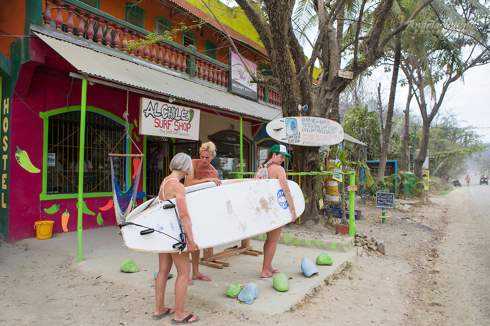 Surf shop owner helping two women carry surfboards together, Santa Teresa, Costa Rica