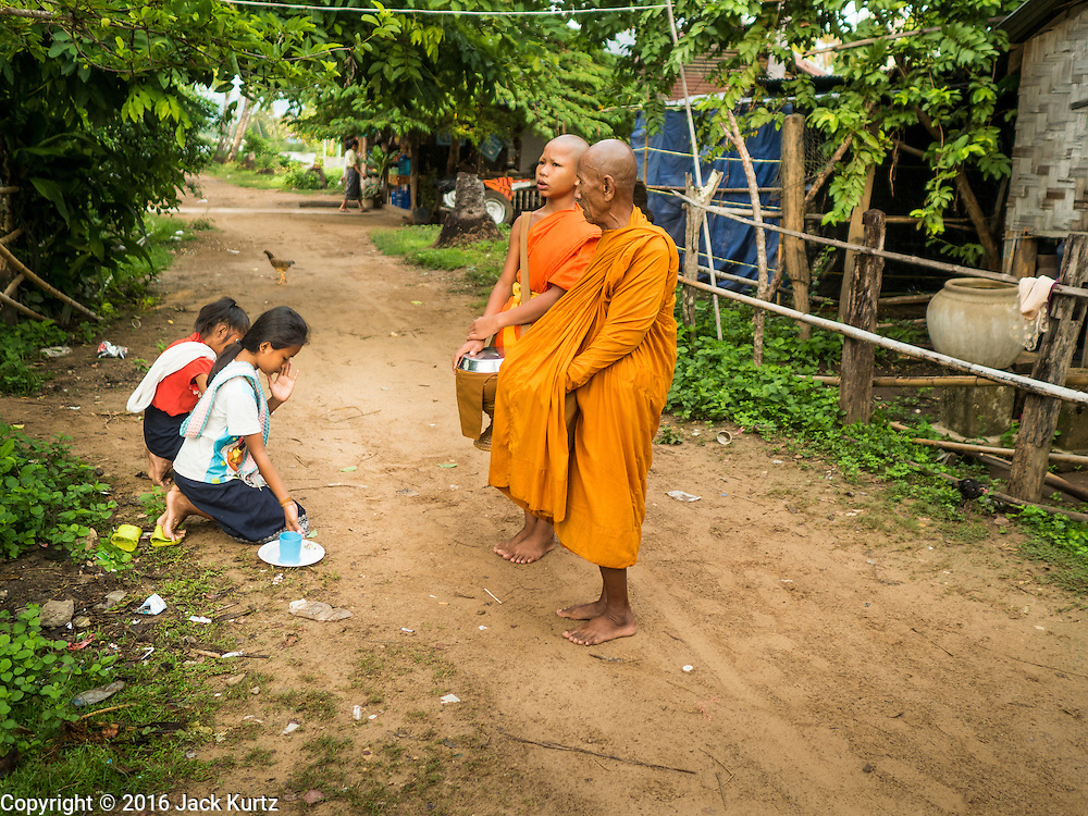 """20 JUNE 2016 - DON KHONE, CHAMPASAK, LAOS:  Girls pray after presenting alms to monks from Wat Khone Nua on their morning alms' rounds, called the """"tak bat"""" in Don Khone village on Don Khone Island. Don Khone Island, one of the larger islands in the 4,000 Islands chain on the Mekong River in southern Laos. The island has become a backpacker hot spot, there are lots of guest houses and small restaurants on the north end of the island.    PHOTO BY JACK KURTZ"""