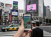 A player is looking for pokemon at the shibuya crossing, the famous intersection outside Shibuya Station. The Japanese version of the game app Pokemon Go was released on July 22, 2016. Japan McDonalds' 3,000 restaurants in Japan will be turned into Pokemon gyms in collaboration with the fast-food chain. 22/07/2016-Tokyo, JAPAN