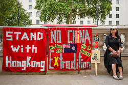 © Licensed to London News Pictures. 01/08/2019. LONDON, UK.  A member of the Hong Kong Chinese community in London with banners during a protest outside the Cabinet Office in Whitehall calling for Boris Johnson, Prime Minister, to intervene and to help Hong Kong.  The former British colony is in its eighth consecutive weeks of protests, which were sparked by a proposed extradition bill that would allow suspects to be sent to mainland China.  Photo credit: Stephen Chung/LNP