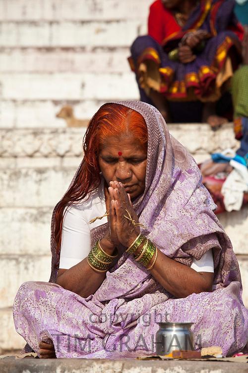 Indian Hindu pilgrims  praying by The Ganges River at Dashashwamedh Ghat in Holy City of Varanasi, Benares, India
